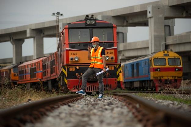 Ingegnere del ritratto sotto controllo e controllo dell'interruttore ferroviario del processo di costruzione.