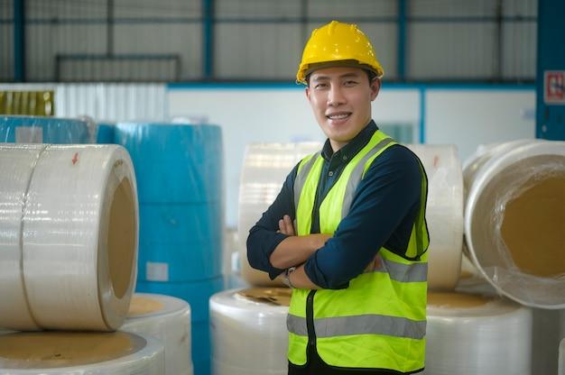 Ritratto di un ingegnere che mette un casco protettivo sulla testa in magazzino