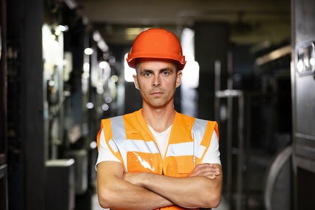 Ritratto di un ingegnere o di un lavoratore che incrocia i bracci che lavorano nella stazione elettrica dell'energia elettrica