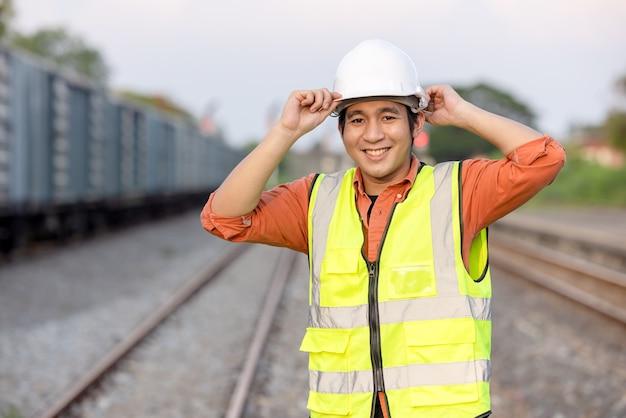 Ritratto ingegnere uomo che lavora sulla ferrovia. ingegnere capo nell'elmetto protettivo nella struttura di manutenzione, concetto di ingegnere e riparatore. sicurezza prima di tutto