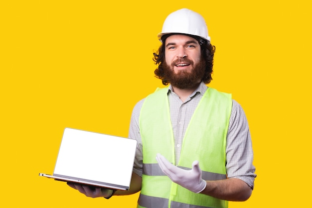 Ritratto dell'ingegnere che indossa il casco e che mostra lo schermo vuoto sul computer portatile