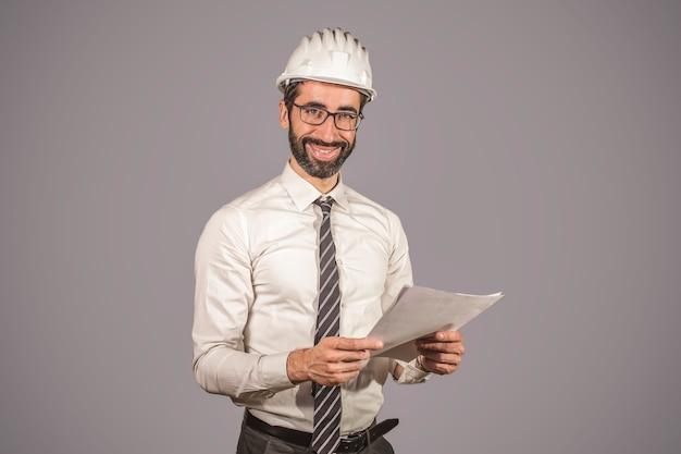 Ritratto dell'ingegnere con documenti di lavoro. sfondo grigio.