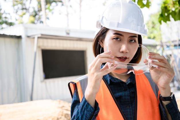 Ritratto di donna ingegnere in piedi e togliersi gli occhiali dopo aver verificato il progetto e il rapporto statistico in loco. vista posteriore dell'appaltatore sullo sfondo di edifici domestici moderni con edificio.