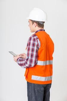 Ritratto del telefono cellulare della holding dell'uomo di ingegneria su priorità bassa bianca