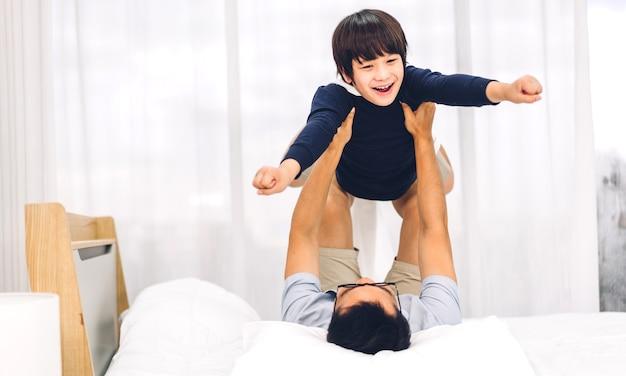 Ritratto di godere di amore felice padre di famiglia asiatico che trasporta piccolo figlio ragazzo asiatico sorridente giocando supereroe e avendo momenti divertenti buon tempo sul letto a casa