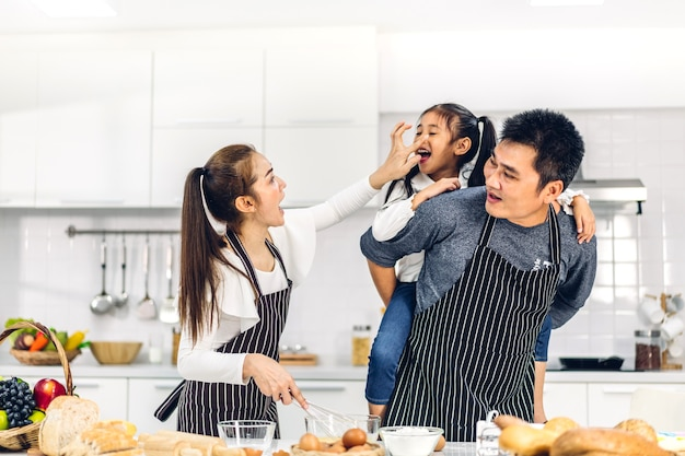 Ritratto di godere di amore felice asiatico padre di famiglia e madre con la piccola ragazza asiatica figlia bambino divertendosi cucinando insieme a cuocere i biscotti e gli ingredienti della torta sul tavolo in cucina