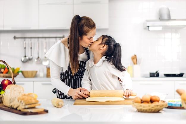 Il ritratto di gode della madre asiatica della famiglia di amore felice e del bambino della figlia della piccola ragazza asiatica divertendosi cucinando insieme ai biscotti e agli ingredienti della torta di cottura sulla tavola in cucina