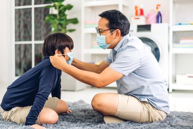 Ritratto di godere di amore felice padre asiatico che indossa la maschera protettiva per il piccolo bambino asiatico in quarantena per coronavirus con allontanamento sociale a casa.