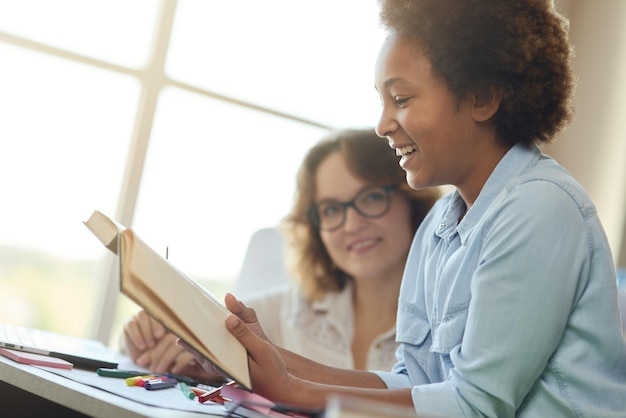 Ritratto di una ragazza adolescente entusiasta di razza mista che legge ad alta voce durante una lezione con la sua insegnante