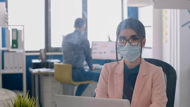 Ritratto di donna imprenditrice che indossa una maschera facciale per evitare l'infezione da coronavirus durante la pandemia globale. colleghi che lavorano in background in ufficio al progetto aziendale nel rispetto del distanziamento sociale
