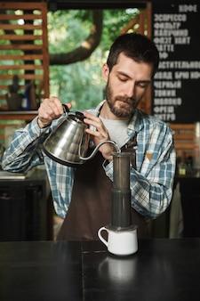 Ritratto di un barista europeo che indossa un grembiule che fa il caffè mentre lavora in un caffè di strada o in un caffè all'aperto