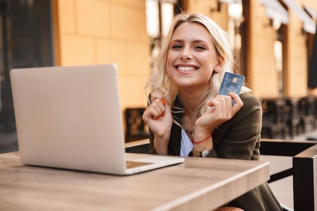Ritratto di donna bionda europea che indossa giacca utilizzando laptop argento e tenendo la carta di credito, mentre è seduto in un caffè all'aperto