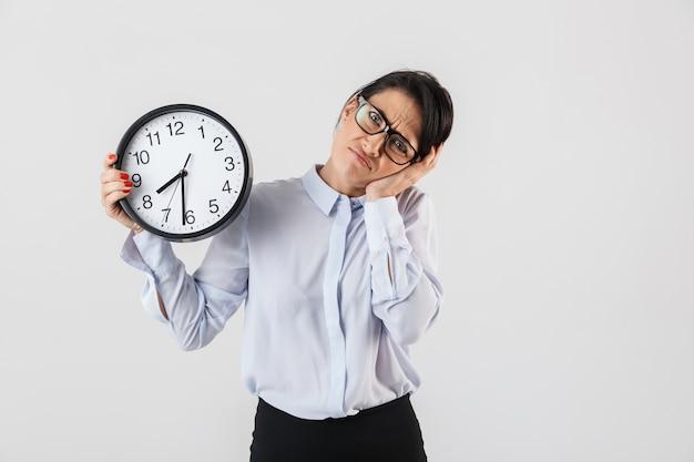 Ritratto della donna di affari europea che indossa occhiali da vista che tengono orologio rotondo in ufficio, isolato sopra il muro bianco