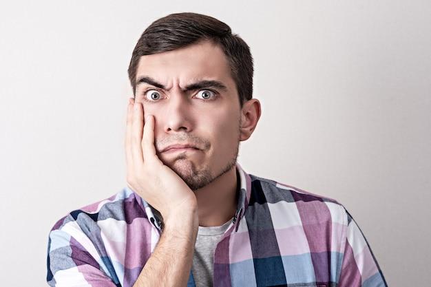 Ritratto di un uomo europeo con una faccia perplessa che si tiene la mano sulla guancia
