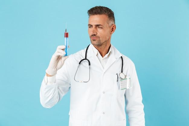 Ritratto di medico europeo con lo stetoscopio in guanti che tengono la siringa, in piedi isolato sopra la parete blu