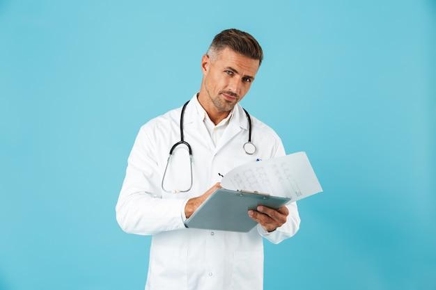 Ritratto di medico europeo con stetoscopio in possesso di tessera sanitaria, in piedi isolato sopra la parete blu