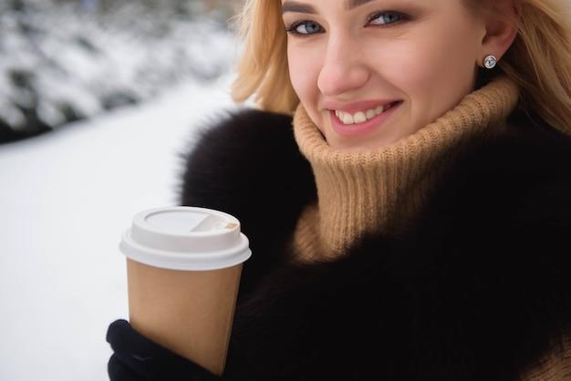 Ritratto della donna alla moda di stile europeo che beve caffè a winter park