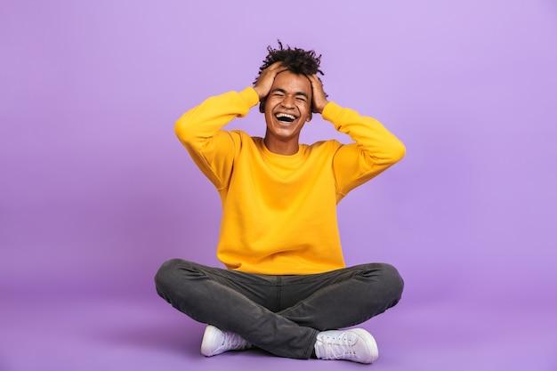 Ritratto di eccitato ragazzo afroamericano che ride e afferra la testa mentre è seduto sul pavimento con le gambe incrociate, isolato su sfondo viola