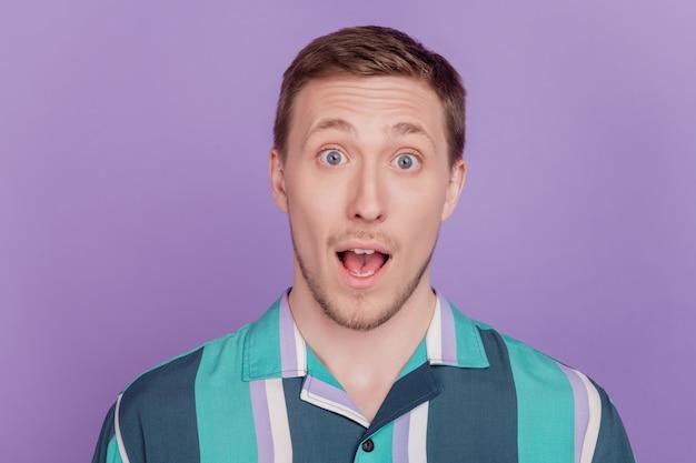 Ritratto di eccitato ragazzo stupito bocca aperta reazione omg su sfondo viola