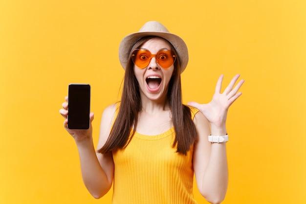 Ritratto di donna eccitata stupita in cappello estivo, occhiali arancioni tengono la bocca spalancata, sembrano sorpresi, tengono il telefono cellulare con schermo vuoto vuoto isolato su sfondo giallo. concetto di emozioni della gente.