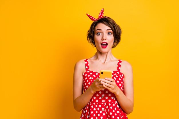 Ritratto eccitato ragazza stupita usa il cellulare ricevi incredibile notifica social network impressionato urlo wow omg indossare gonna retrò a pois rosso isolato muro di colore brillante lucentezza