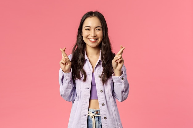 Ritratto di eccitata giovane ragazza coreana attraente che ha fede che tutto sia buono, incrocia le dita mentre esprimi il desiderio, sognando il desiderio che si avvera, sfondo rosa.