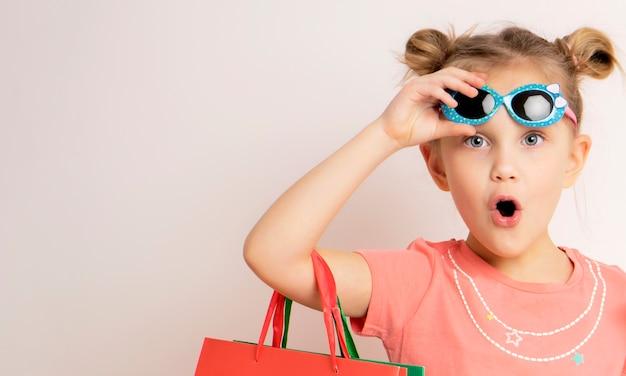 Ritratto di un vestito da portare della bella bambina emozionante e degli occhiali da sole che tengono i sacchetti della spesa