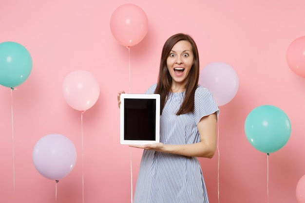 Ritratto di eccitata bella giovane donna che indossa abito blu che tiene computer tablet pc con schermo vuoto vuoto su sfondo rosa pastello con mongolfiere colorate. concetto di festa di compleanno.