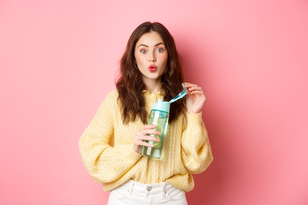 Ritratto di donna bruna eccitata di acqua potabile con limone dalla bottiglia di sport personale, sguardo incuriosito e interessato alla telecamera, in piedi contro il muro rosa.