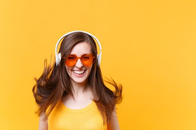 Ritratto di donna comica divertente risata allegra eccitata in occhiali arancioni in cuffie con capelli svolazzanti isolati su sfondo giallo. persone sincere emozioni, concetto di stile di vita. area pubblicitaria