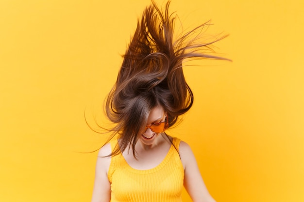 Ritratto di eccitata risata allegra divertente donna comica in bicchieri arancioni con capelli svolazzanti copia spazio isolato su sfondo giallo. persone sincere emozioni, concetto di stile di vita. zona pubblicità.