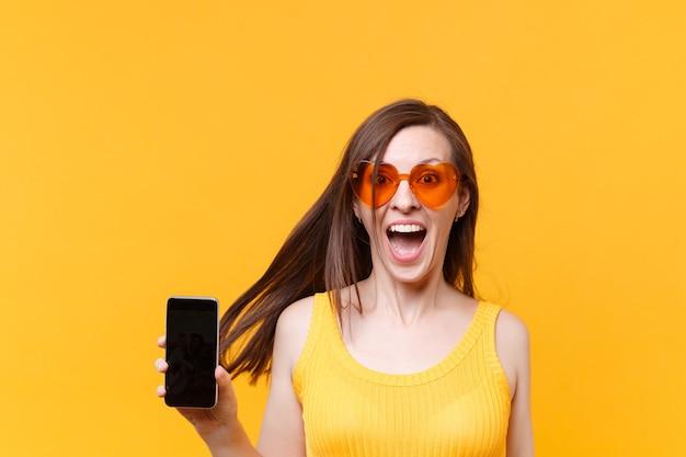 Ritratto di donna comica divertente risata allegra eccitata in occhiali arancioni con capelli svolazzanti tenere il telefono cellulare con lo spazio della copia schermo vuoto vuoto isolato su sfondo giallo. zona pubblicità.