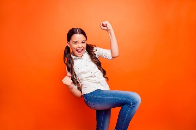 Ritratto di entusiasta estatica bambina vincere concorso sportivo gridare sì alza i pugni sentire contenuto indossare abiti in stile casual isolato su sfondo di colore arancione