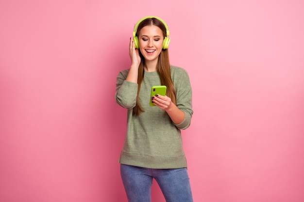 Il ritratto della ragazza energica eccitata usa lo smart phone ascolta la musica