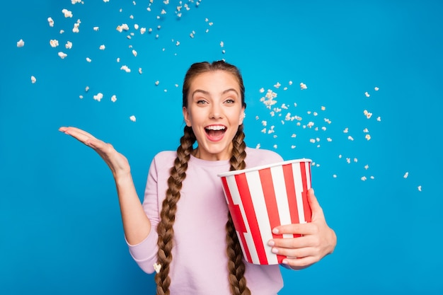 Ritratto di ragazza entusiasta eccitata tenere la scatola con popcorn volante che cade nel vento che soffia mentre si guarda la serie tv canale urla wow omg indossare il ponticello rosa isolato su sfondo di colore lustro