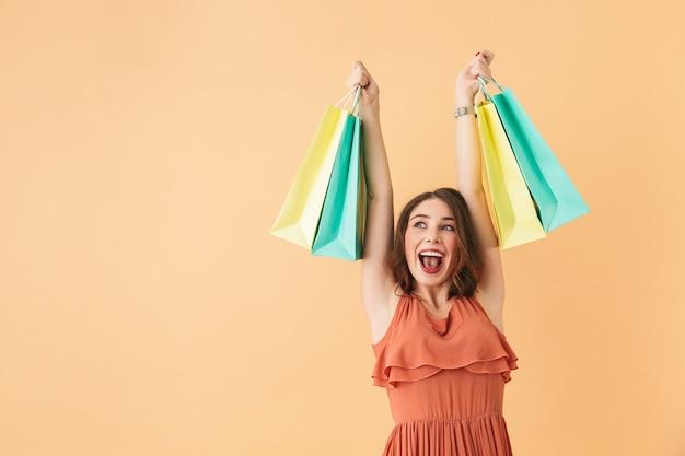Ritratto della ragazza eccitata 20s che trasportano i sacchetti della spesa di carta variopinti, mentre levandosi in piedi isolato