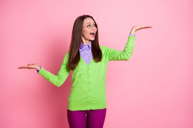 Ritratto di ragazza eccitata tenere la mano copyspace indossare camicia verde pantaloni viola isolato sfondo di colore pastello