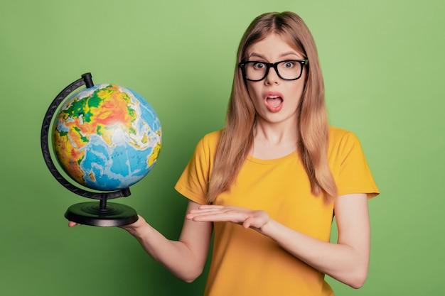 Il ritratto di una ragazza eccitata, insegnante di geografia, mostra una t-shirt gialla con occhiali da sole
