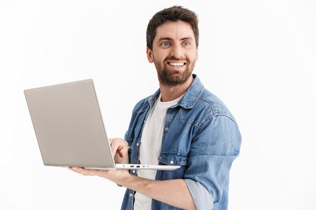 Ritratto di un uomo barbuto bello eccitato che indossa abiti casual in piedi isolato, utilizzando un computer portatile