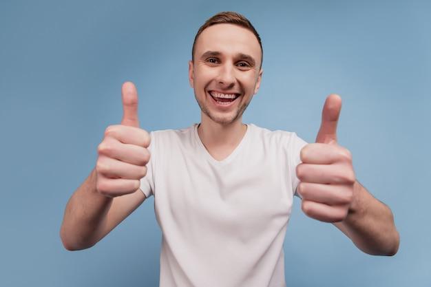 Il ritratto di un bel ragazzo eccitato mostra due braccia con i pollici in su come un bel sorriso isolato su uno sfondo di colore blu