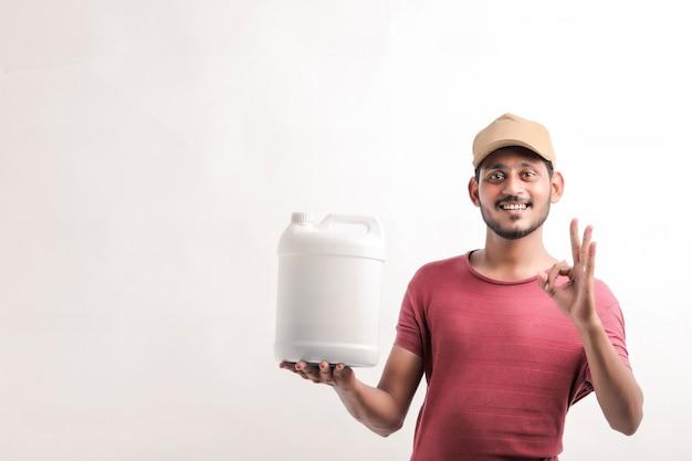 Ritratto di un giovane fattorino felice eccitato in berretto in piedi su sfondo bianco e tenendo la bottiglia in mano.