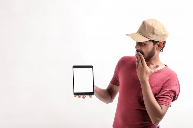 Ritratto di giovane fattorino felice emozionante in protezione che controlla fondo bianco. guardando la fotocamera che mostra il display del telefono cellulare.