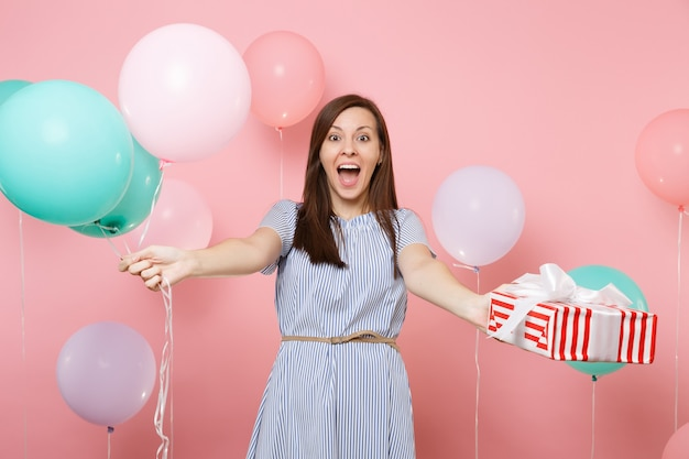Ritratto di giovane donna felice eccitata che indossa un abito blu che tiene in mano una scatola rossa con un regalo presente e mongolfiere colorate su sfondo rosa brillante. festa di compleanno, concetto di emozioni sincere della gente.