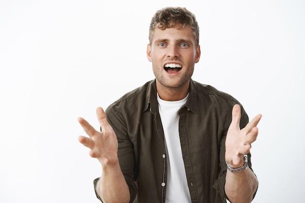 Ritratto di un bell'uomo felice eccitato e impressionato che gesticola con le mani sul corpo sorridendo entusiasta e incuriosito mentre racconta di un prodotto fantastico sul muro grigio