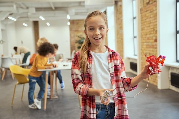 Ritratto di una bambina eccitata che sorride alla telecamera e mostra il suo robot fai da te mentre sta in piedi in a
