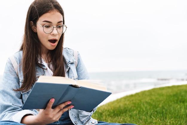 Ritratto di una bella ragazza adolescente eccitata che indossa occhiali che esprime sorpresa mentre legge un libro e si siede sull'erba verde in riva al mare