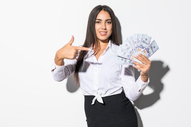 Ritratto di una ragazza soddisfatta eccitata che tiene le banconote dei soldi e del dito puntato isolato su bianco