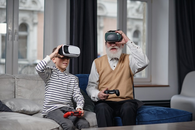Ritratto dell'uomo senior emozionante che usando i vetri di vr che si siedono sul sofà a casa con il nipote di risata accanto a lui