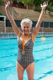 Ritratto di donna senior eccitata con medaglie d'oro al collo in piedi a bordo piscina
