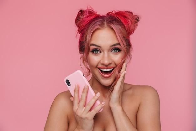 Ritratto di una giovane donna senza camicia eccitata con un'acconciatura colorata che sorride e tiene in mano uno smartphone